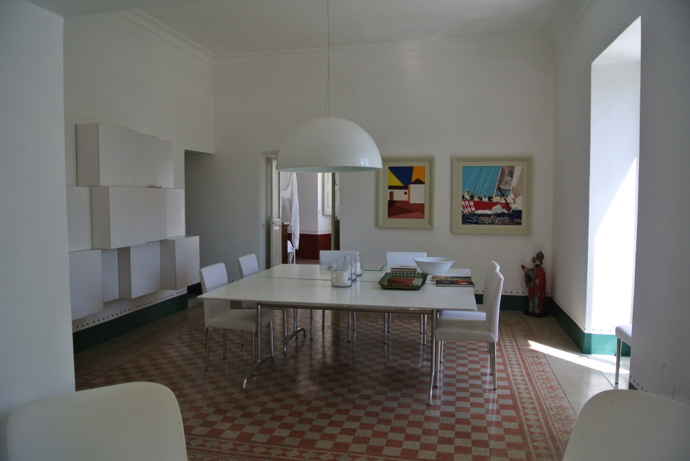 "Dining room with original marble-chip floor. De Padova ""Shine Table', Flos 'Sky Garden' lamp, Pollack chairs."