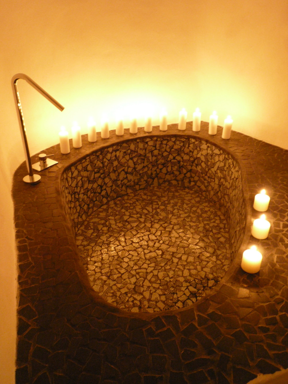 Relaxation tub with a mosaic effect using the house's original marble-chip tiles.